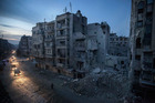 Night falls on a Syrian rebel-controlled area as destroyed buildings, including Dar Al-Shifa hospital, are seen. Photo / AP