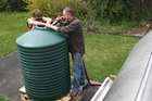 FILL 'ER UP: Jason Day and David Gilberd fill a 1000-litre water tank behind Raetihi doctors' surgery building.