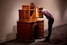Auckland Museum's Finn McCahon-Jones examines the intricate desk by master craftsman William Seuffert, which cost $500,000 to bring back to New Zealand. Photo / Dean Purcell