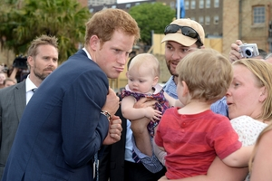 Prince Harry shows his best mad-uncle funny face for a young child in the large crowd greeting him during the International Fleet Review in Sydney. Photo / AP