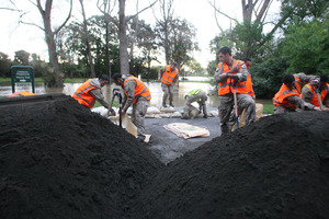 Soldiers work feverishly to sandbag the flooded Matarawa stream behind them from encroaching further into Kowhai Park in Wanganui East.