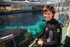 Judy Bailey manages a nervous smile as she sits on the edge of the aquarium's shark pool. Photo / Greg Bowker