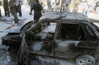 A damaged vehicle smolders after firefighters extinguish a fire on it following two mortar rounds struck the Abu Roumaneh area in Damascus, Syria. Photo / AP