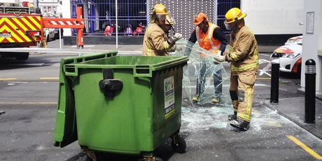 Fire crews clean up glass from Rydges hotel car park, which was blown out by high winds. Photo / Greg Bowker