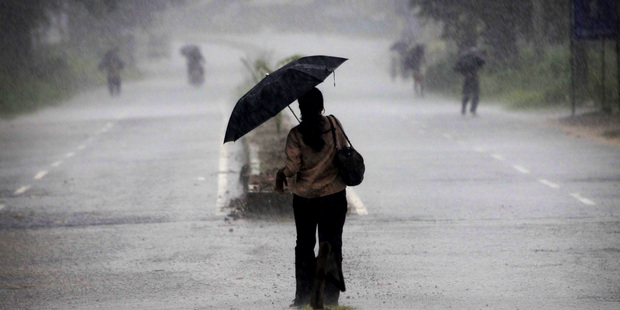 An Indian woman holds an umbrella as she heads towards a cyclone shelter near Chatrapur in Ganjam district. Photo / AP