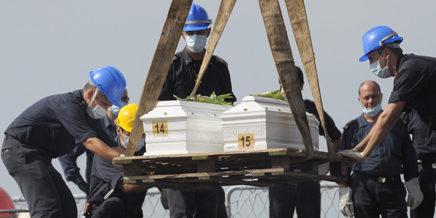 The caskets of two children who died when their boat capsized off in the Canal of Sicily are lifted to be embarked on a Italian Navy ship at the Lampedusa island harbor. Photo / AP