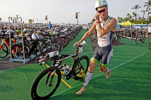 Competitor Frederik Van Lierde, of Belgium, runs with his bicycle on the Kailua Pier to begin a 112-mile ride in the Ironman World Championship Triathlon on Saturday. Photo / AP.