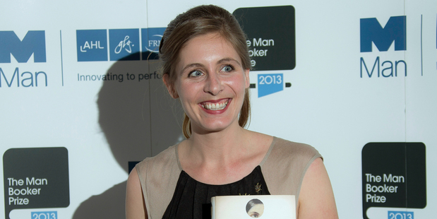 New Zealand author Eleanor Catton poses after being announced the winner of the Man Booker Prize for Fiction, holding her prize and her book for the photographers. Photo / AP