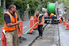 Workers roll out fibreoptic cable cover in Faraday Street, Napier. Photo / Glenn Taylor