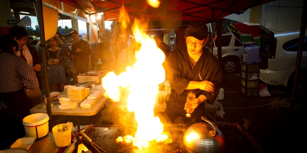 Chris Pei cooks up a storm in his stall at the Sunday night market at Glenfield. Photo / Richard Robinson