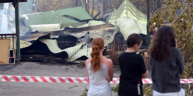 Children look at a house burnt out by bushfires in Winmalee in Sydney's Blue Mountains. Photo / AFP