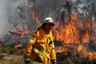NSW Rural Fire Service firefighter Garry Reid from the Medlow Bath brigade puts in containment lines on the Darling Causeway near the township of Bell in the Blue Mountains. Photo / AAP