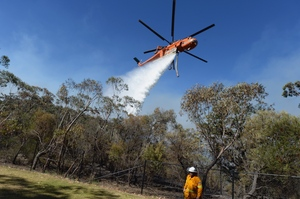 A firefighter looks on as air crane Elvis drops water at the Linksview Rd fire near Faulconbridge. Photo / AAP