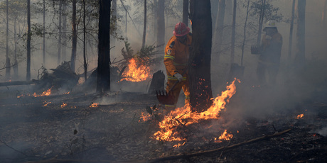 NSW Rural Fire Service crews mop up an area after stopping a fire from impacting on a property at Bilpin, in the Blue Mountains. Photo / AAP