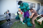 Zion Fernando, 7, waits for his dad Eli to get into his Incredible Hulk costume with help from Andrew Pablo, left, and Erick Javier. Photo / Richard Robinson
