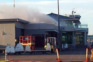 Passengers wait in the evacuation area in front of Hawke's Bay Airport yesterday, as smoke billows from the roof of the terminal. Photo / Supplied.