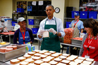 President Barack Obama puts a bologna sandwich in to a Ziploc bag at Martha's Table, which assists the poor and where furloughed federal employees were volunteering. Photo / AP
