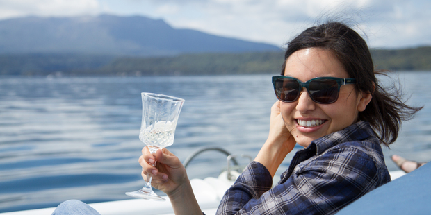 Nadia Lim enjoying Lake Tarawera from the bow of the charter boat. Photo / Carlos Bagrie