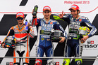 MotoGP riders, from left, Dani Pedrosa of Spain, Jorge Lorenzo of Spain and Valentino Rossi of Italy pose on the winners podium after the Australian motorcycle Grand Prix in Phillip Island. Photo / AP
