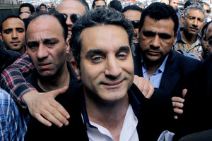 A bodyguard secures popular Egyptian television satirist Bassem Youssef, who has come to be known as Egypt's Jon Stewart. Photo / AP