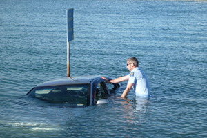 Mel Hunter, police officer, wades out to check the submerged car found in Napier yesterday.  Photo / Supplied