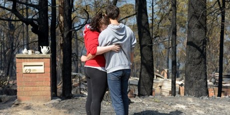 Amy Hubbard and her partner Adam Ilhan stand in front of the burnt out ruins of her parents' home which was destroyed by bushfires in Winmalee in Sydney's Blue Mountains. Photo / AFP