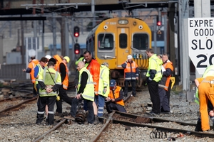 OFF TRACK: KiwiRail staff inspecting debris and damage after the passenger unit of a commuter train derailed. PHOTO/MARK MITCHELL