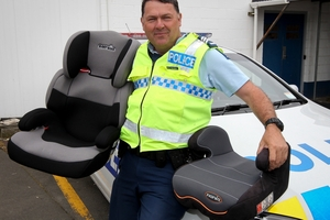 DRIVEN: The driving force behind the new child restraint legislation, Sergeant Nigel Hurley, with a couple of seating options for children up to the age of 7. PHOTO/GLENN TAYLOR HBT134219-01