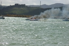 A plume of smoke floats across Whangarei Harbour as a trimaran burns. Photo / Bryn Heatley