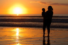 Sheridan Waitai and her nephew watch the sun go down at Ahipara in Northland. Photo / Mark Mitchell