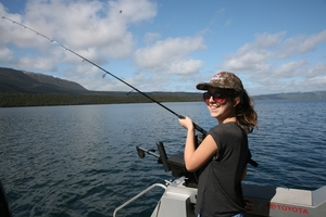 Katie Thomas plays a trout hooked while trolling on Lake Tarawera.