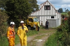Rural firefighters guard one of two threatened houses on Mangakahia Rd.