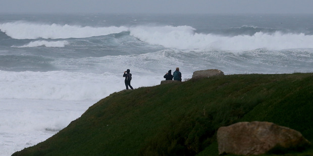 People stop to look at the stormy seas off Fistral Beach. Photo / Getty Images