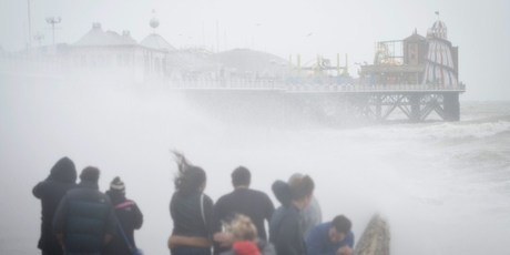 People watch as large waves crash against the walls of Brighton seafront, in southern England, as a predicted storm starts to build. Photo / AFP