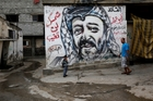 Palestinians walk past a mural depicting Yasser Arafat at Shati Refugee Camp, in Gaza City. Most Palestinians blame Israel for his death.Photo / AP