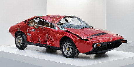 A Wrecked Ferrari Dino 308 GT4 is the center piece at an Art Exhibition