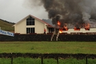 FLAMES: Smoke pours from Mokau Marae. PHOTO/LEANNE YENDALL-ROSS