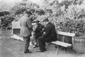Sir Joseph Ward (left) and Prime Minister William Massey hear out a soldier on the Western Front.