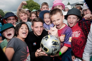YOUNG FOOTBALLERS: Liam Higgins, WaiBOP United defender, entertains Otonga School pupils yesterday as part of the build up to WaiBOP's debut match in Rotorua. Also pictured is pupil Byron Macrae, 6 (with ball). PHOTO/BEN FRASER