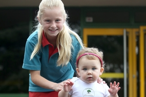 Briar Hancox, 9, of Pinehill School in Albany, with 13-month-old Zoe Wilson of Sunnynook at the celebration. Photo / Jason Oxenham
