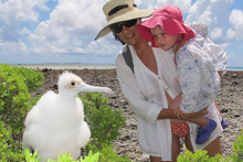 Mother and daughter eye a frigatebird chick in Suwarrow, Cook Islands.