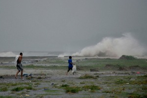 Residents sift through the shoreline amidst a storm surge brought about by powerful typhoon south of Manila.Photo / AP