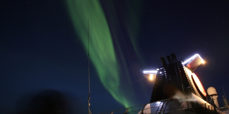 The Northern Lights colour the sky above the ship.