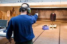 A marksman shoots a handgun at a bulletproof suit made by Garrison Bespoke tailors. Photo / AP