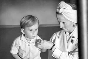Physical therapist Estrid Dane supports two-year-old Anthony Bull who is suffering from toickets in 1943 .Photo / AP