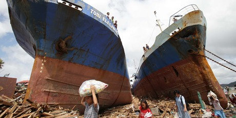 Survivors pass by two large boats after they were washed ashore by strong waves caused by Typhoon Haiyan. Photo / AP
