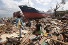 Residents walk beside a large ship that was washed ashore by strong waves caused by Typhoon Haiyan in Tacloban city. Photo / AP