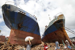 Survivors pass by two large boats after they were washed ashore by strong waves caused by Typhoon Haiyan in Tacloban city. Photo / AP