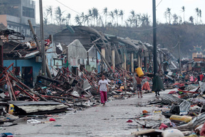 Residents walk past damaged structures caused by typhoon Haiyan. Photo / AP