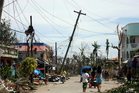 Residents walk past the devastation caused by Typhoon Haiyan. Photo / AP